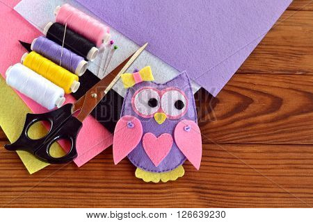 Felt owl, felt sheets, scissors, thread, needle, pins on a brown wooden background