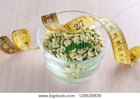 Green coffee beans in a cup with measuring tape on white wooden table