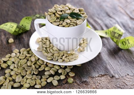 Green coffee beans in a white cup with measuring tape on wooden table
