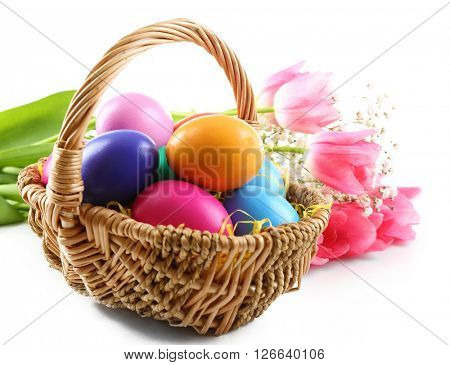 Multicoloured Easter eggs in wicker basket isolated on white
