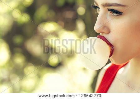 young pretty woman with chewing gum in the garden with fresh spring leaves on trees on blurred natural background