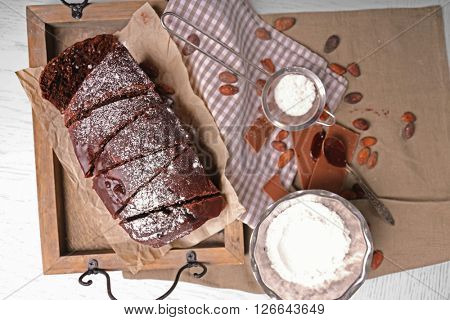 Chocolate sliced cake with icing and powdered sugar on a tray