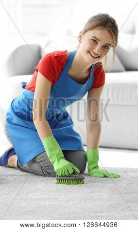 Cleaning concept. Young woman cleans carpet in the room