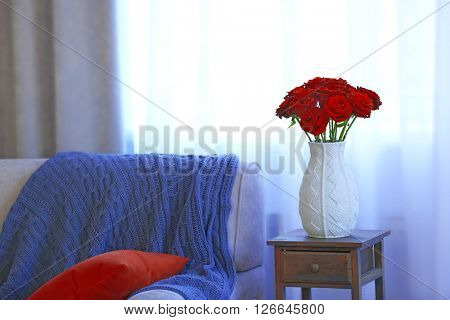 Vase of red roses on a bedside table in the room