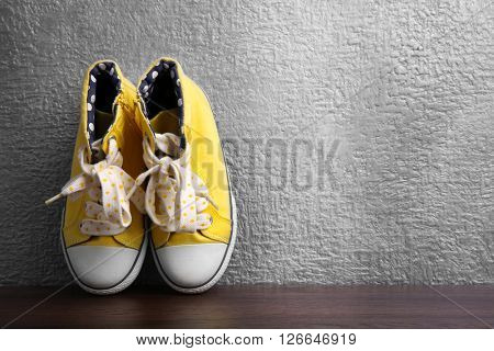 Yellow gumshoes for girls on grey textured background