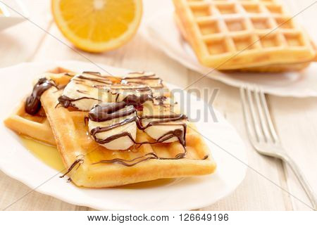 Sweet waffels and banana slices with melted chocolate.selective focus on the front waffels