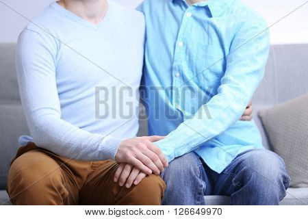 Two men sitting on sofa and holding each other hands