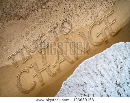 Time to Change written on the beach