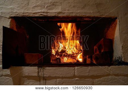 Red and orange crackling fire in russian wood stove