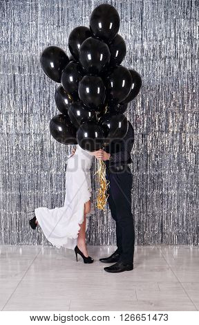 the bride and groom hiding behind balloons. Wedding photo.
