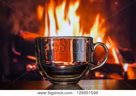 transparent glass mug on a table on a background of fire fire