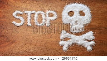 Unhealthy concept. White sugar objects on brown wooden background.