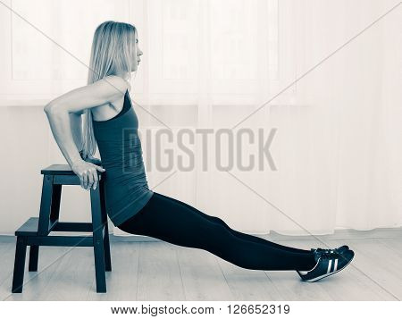 A woman in a a light room performs pushups on the box