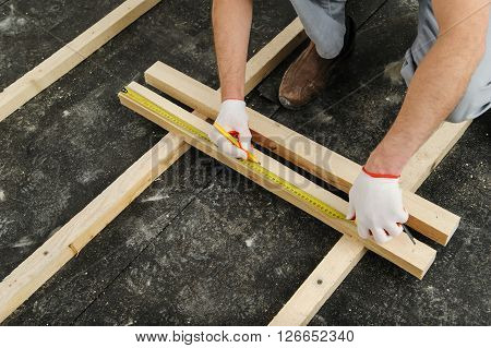 Worker measures off a wooden beam to cut it further.