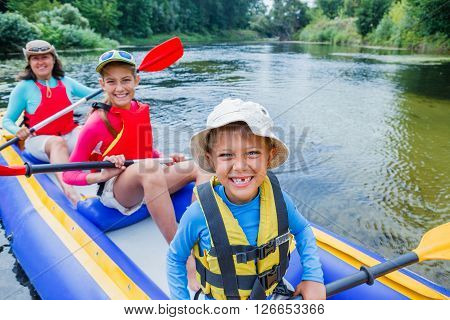 Active happy family. Boy with his sister and mother having fun together enjoying adventurous experience kayaking on the river on a sunny day during summer vacation