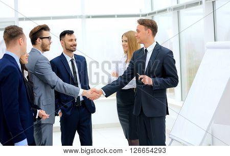 Successful businessmen handshaking after presentation