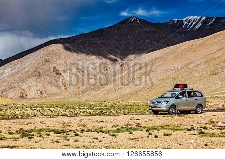LADAKH, INDIA - SEPTEMBER 8, 2011: Modern MPV car on road in Himalayas mountains