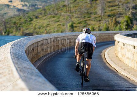 MARATHON GREECE- JUNE 6 2012: Cyclist crossing the Marathon dam