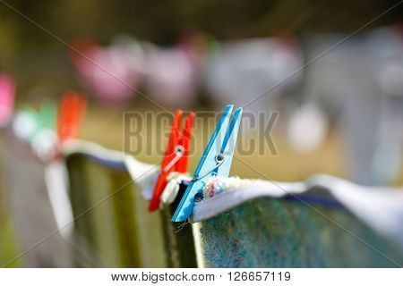 Clothespins holding laundry on the drying line drying clothes outside on fresh air wind and sun. Housework family life household natural living and lifestyle concept.