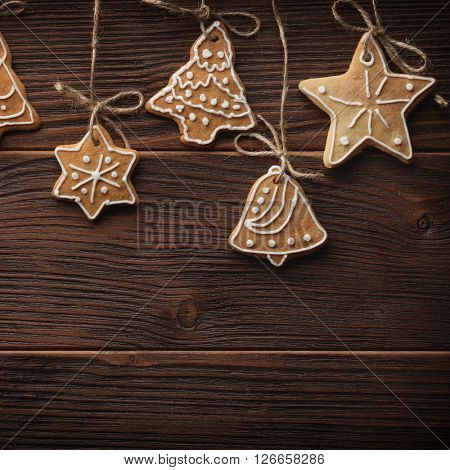 Gingerbread cookies hanging over wooden background. Closeup