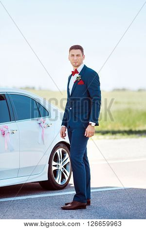 Portait of a young handsome man in suite near white widding decorated car.  Gorgeous guy, outdoors