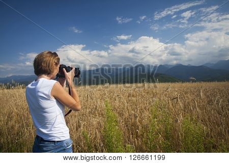 Traveler girl photographing ripe wheat field in bright sun rays, autumn harvest season, travel and tourism concept