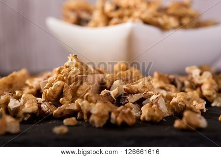 Spilled Walnuts In Front Of Square White Bowl