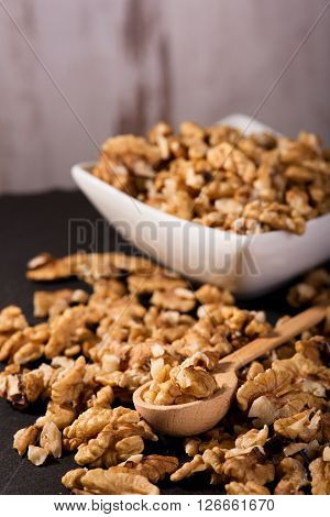Spoon With Walnuts Which Are Too Spilled Around On Slate