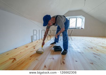 Wooden floor varnished. Worker with paint roller.