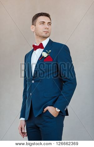 Portait of a young handsome man in suite. Gorgeous guy on gray background