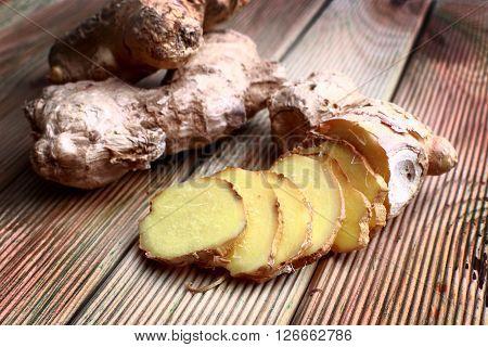 Close-up shot of sliced ginger on wood background