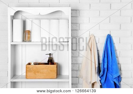 Bathroom set with towels, boxes and dispensers on a shelf in light interior