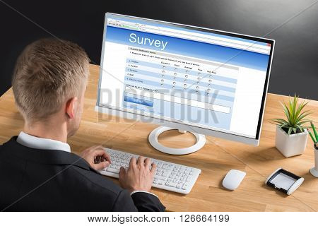 Businessman Filling Online Survey Form On Computer