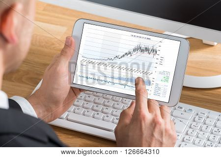 Male Stock Market Broker Working On Digital Tablet