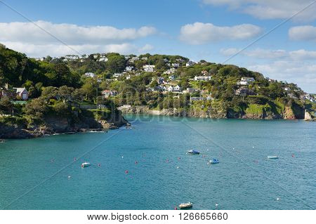 Salcome estuary Devon UK with boats and blue sky and houses on the hillside
