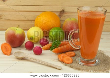 Glass of carrot juice and carrots on the wooden table. Healthy juice full of vitamins and fiber. Diet Food. Carrot segments on a wooden background.