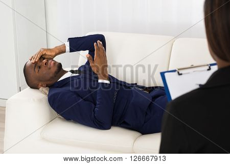 Patient Laying On Couch In Front Of Psychiatrist