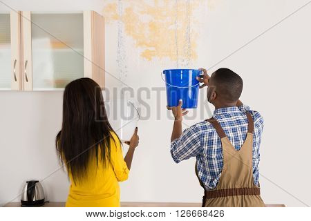 Young Woman And Worker Collecting Water In Bucket From Ceiling