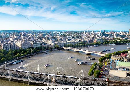 LONDON, UK - JUNE 6, 2015: Aerial cityscape  over the river Thames  between Haugerford  and Waterloo Bridges with tourist pleasure boats in late afternoon time.  In the bottom right part of the image visible  promenade at Lambeth area near Royal Festival