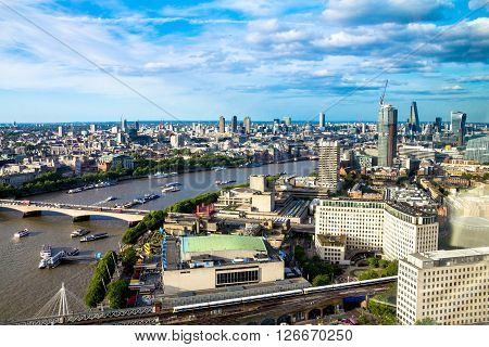 LONDON, UK - JUNE 6, 2015: Aerial cityscape  over the river Thames  between Haugerford  and Waterloo Bridges with tourist pleasure boats in late afternoon time. In the bottom right part of the image visible  promenade at Lambeth area near Royal Festival H