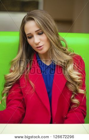 Portrait close up of young beautiful blonde woman in red coat