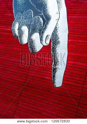 LONDON UK - JUNE 6 2015: Gray image left man's hand with the index finger pointing down on the red painted wooden planks background
