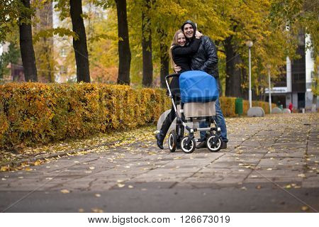 Young happy parents walking in autumn park with a pram