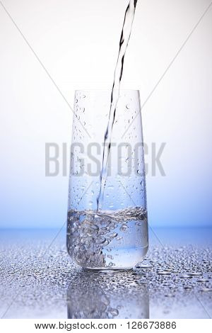 Water Pouring Into One-third Full Drinking Glass