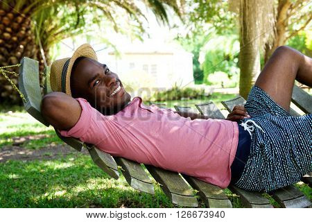 Young African Man Relaxing Outdoors On A Hammock