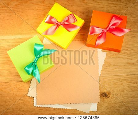 Three gift boxes with blank gift tag on wooden background