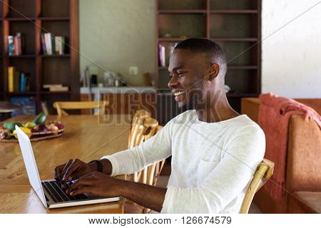 Young African Man Working On Laptop Indoors