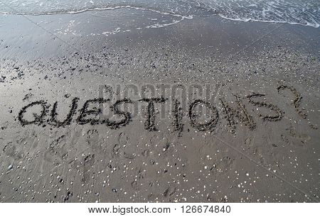 Word Questions With Question Mark Written In Large Letters On The Sand Of The Sea In Summer