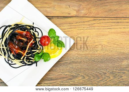 Black Spaghetti with Cuttlefish Ink, Tomato and Basil. Mediterranean and Asian Cuisine. Studio Photo