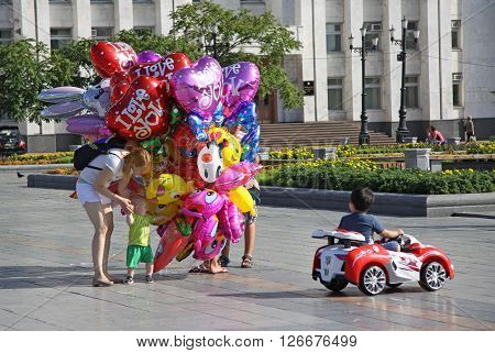 KHABAROVSK RUSSIA - AUGUST 16 2013: Balloon Seller and a buyer with children on the Lenin square in Khabarovsk